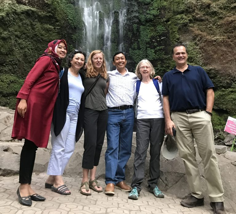 Six people standing in front of a waterfall for a group photo
