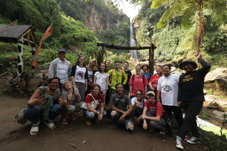 students join Indonesian excursion to local waterfall